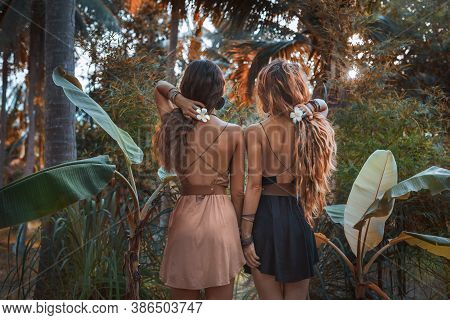 Two Beautiful Young Women In Elegant Dresses At Tropical Background
