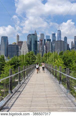 New York, Usa - May 21, 2018: People Walking On An Elevated Walkway Towards The Brooklyn Bridge Park