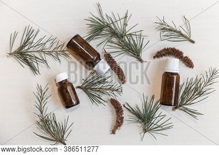 Top View Bottles With Cedar Oil. Aromatherapy And Natural Cosmetics Concept Background