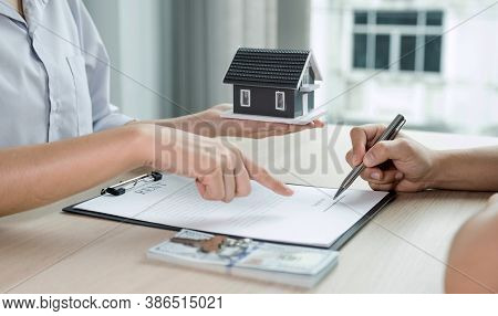 Buyer Hand Signs Contract After Real Estate Agents Explains A Business Contract, Lease, Purchase, Mo