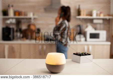 Having A Conversation Unsing Smartphone And Ejoying Aromatherapy From Diffuser With Essential Oils.