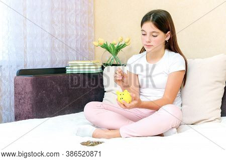 Ute Young Caucasian Girl Deposit Coin Into Piggy Bank For Future Life Sitting On Sofa In Living Room