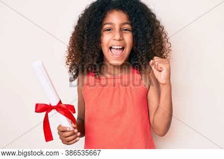 African american child with curly hair holding graduate degree diploma screaming proud, celebrating victory and success very excited with raised arms