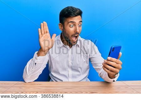 Handsome hispanic man doing video call waving to smartphone afraid and shocked with surprise and amazed expression, fear and excited face.