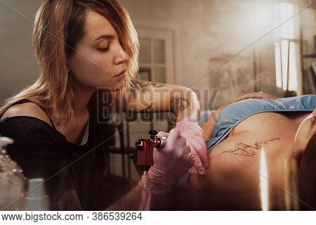 Pretty Girl Lying On Bed And Waiting While Tattoo Master Finish Drawing On Her Shoulder In Warm And