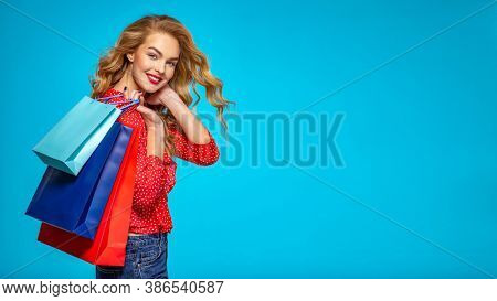 Happy young woman holds bags with a purchases. Beautiful trendy girl with a colorful shopping bags. Model in a red shirt over blue background holding bags with gifts. Happy caucasian woman.