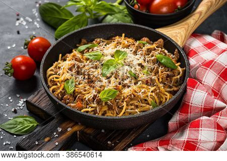Pasta Bolognese, Spaghetti With Meat Ragout In Tomato Sauce In The Skillet At Black Table. Italian C