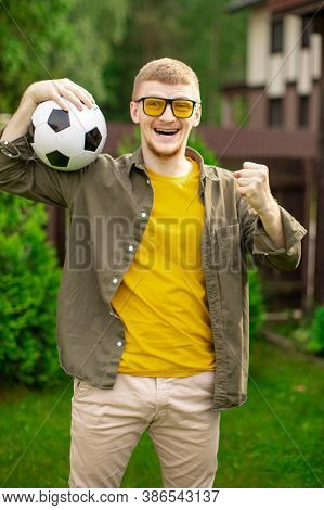 Excited Young Man Holding Soccer Ball Smiling And Screaming, Happy Male Football Fan Support Sport T