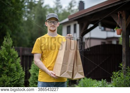 Uniformed Courier Holds Paper Bags Of Food In Open Air Looking At Camera. Delivery Right To Your Doo