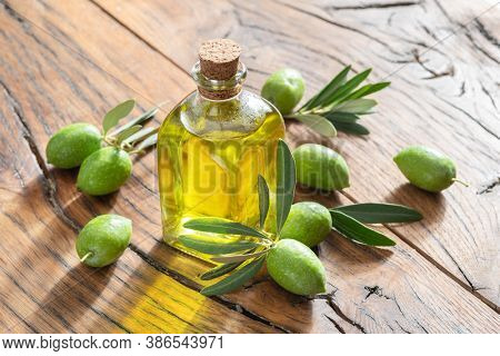 Green natural olives with bottle of olive oil on a vintage old wooden table.