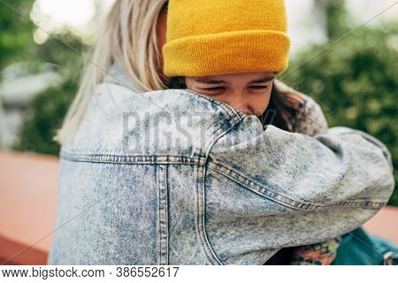 Joyful Little Girl In Yellow Cap Hugging And Laughing With Her Mom Together  In The Park. Happy Kid