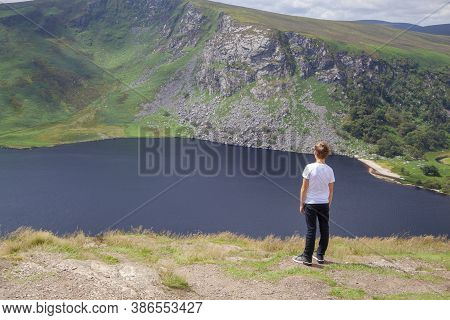 A Boy Admiring A View To A Lough Tay In Wicklow Mountains National Park In Ireland