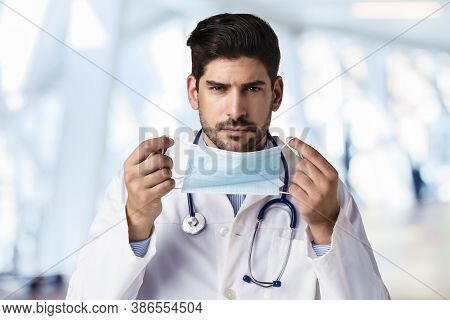 Hot Of Male Doctor Putting On Face Mask For Prevention While Standing In The Hospital's Foyer.