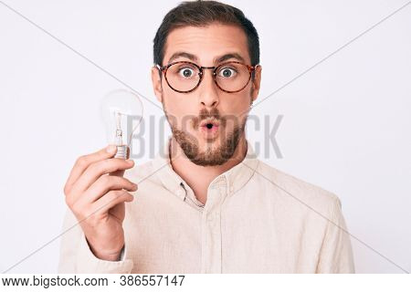 Young handsome man holding lightbulb for inspiration and idea scared and amazed with open mouth for surprise, disbelief face