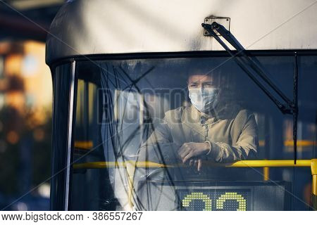 Man Wearing Face Mask And Looking From Window Of Tram. Themes Public Transportation In New Normal, C
