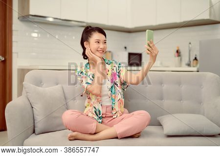 Woman Sitting Sofa Home Phone Holding Hand Makes Selfie Photographs Broadcasting Smile Positive