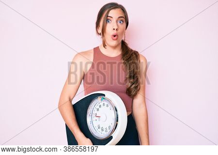 Beautiful young caucasian woman holding weight machine to balance weight loss scared and amazed with open mouth for surprise, disbelief face