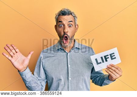 Middle age grey-haired man holding life message paper scared and amazed with open mouth for surprise, disbelief face