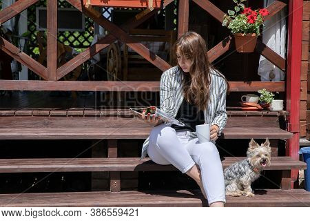 Young Beautiful Woman Resting Outdoors In Morning, Reading Magazines On Porch Of Country House, Fema