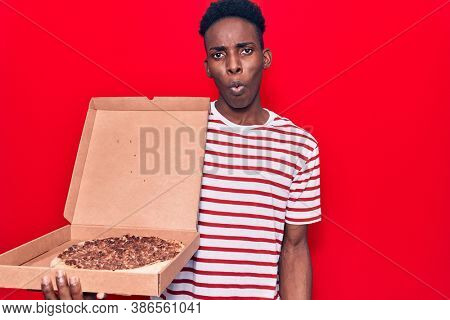 Young african american man holding delivery pizza box scared and amazed with open mouth for surprise, disbelief face