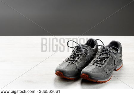 trekking sneakers with red sole, gray copy-space background
