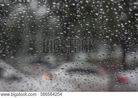 Rain Drops On Car Windshield On Rainy Days On Blur Traffic Jams On The Road Background.