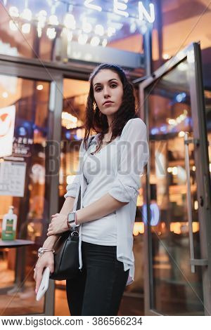 Bright Light Falls On A Young Woman In The Evening City.