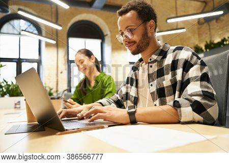 Young Smart Guy Wearing Eyeglasses Working On Laptop While Sitting At Desk With His Female Colleague