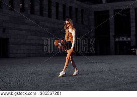 Lifestyle Portrait Of Young Woman With Longboard.