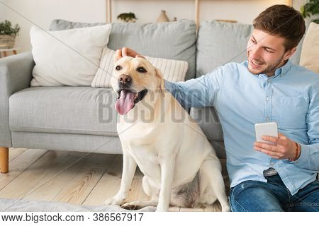 Animal Love And Care Concept. Happy Guy Holding Mobile Phone Sitting On The Floor With Dog And Fondl