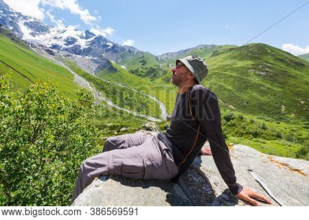 Relaxing man in the mountains at sunrise