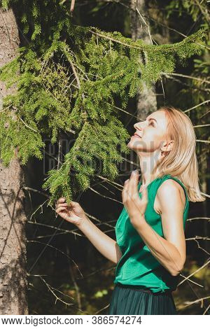 Blonde woman with green blouse and skirt enjoy sun beams near the spruce tree in dark forest during sunny early autumn day