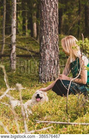 Blonde Woman Playing With Dog In Dense And Dark Forest During Early Autumn Time