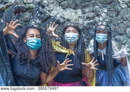 Three Happy Young Women In Witch Halloween Costumes On Coronavirus Year. Girls Are Playing Trick Or
