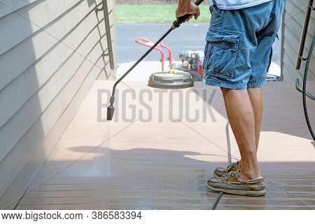 Caucasian Man Spraying Outdoor Wooden Deck With Pressure Washer