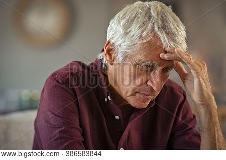 Tired and stressed old man with hand on head with headache. Senior retired man at home feeling worried about health problems. Depressed elderly man sitting with head pain suffers from loneliness.