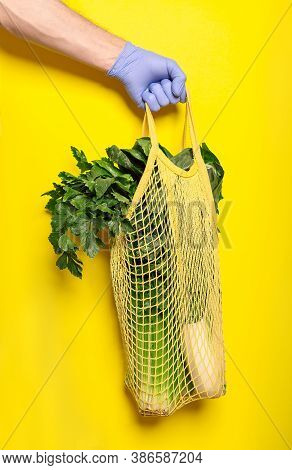A Volunteer Holds Food In A Mesh Bag On A Yellow Background