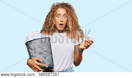 Beautiful caucasian teenager girl holding paper bin full of crumpled papers scared and amazed with open mouth for surprise, disbelief face