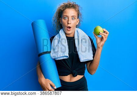 Beautiful caucasian teenager girl holding yoga mat and green apple afraid and shocked with surprise and amazed expression, fear and excited face.