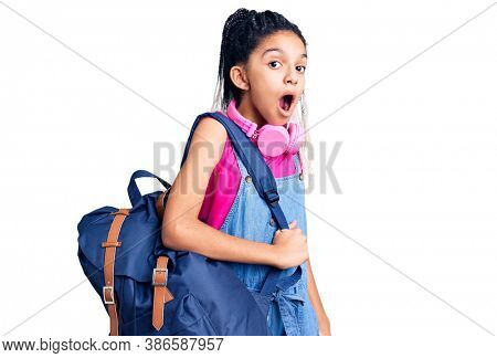 Cute african american girl holding student backpack using backpack scared and amazed with open mouth for surprise, disbelief face