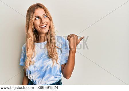 Beautiful blonde young woman wearing tye die tshirt pointing thumb up to the side smiling happy with open mouth