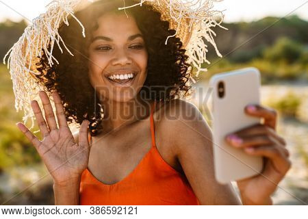 Image of pretty optimistic cheerful young african woman talking by videocall by mobile phone at the beach outside