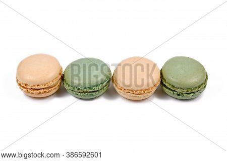 Green Pistachio And Yellow Vanilla French Macarons In A Row Isolated On White Background