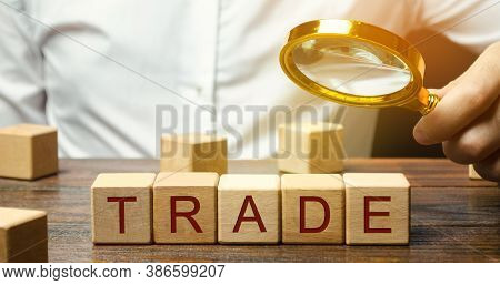 Businessman Holds A Magnifying Glass Over The Word Trade. Business Market And Finance Concept. Trans