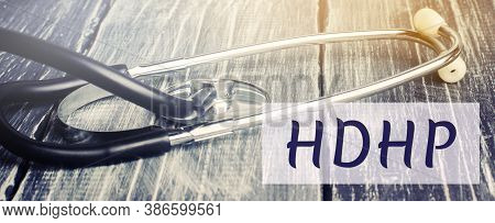 Stethoscope And Inscription Hdhp. High-deductible Health Plan Concept. Lower Premiums And Higher Ded