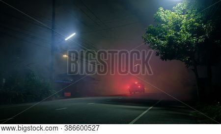 Pickup Truck Drive Into Fog On Empty Road With Red Taillight In Silent Town