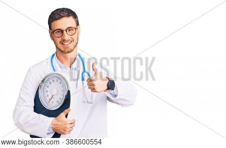 Handsome young man with bear as nutritionist doctor holding weighing machine smiling happy and positive, thumb up doing excellent and approval sign