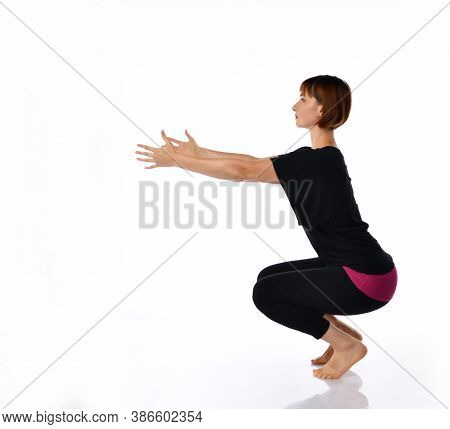 Woman In Tight Sportswear Doing A Deep Squat Side Portrait. Girl Squatting Squats. The Girl Is Engag