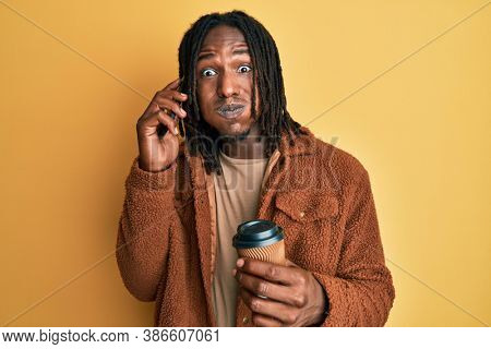 African american man with braids having conversation talking on the smartphone puffing cheeks with funny face. mouth inflated with air, catching air.