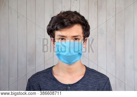 Young Man In Medical Facemask Looking At Camera. Coronavirus, Covid-19 Outbreak. Brown Eyes Of 15 Ye